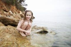 蹲下在岩石的女孩由海 库存图片