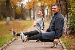 蹲下在平衡用播种手的街道的一只脚的一对愉快的年轻夫妇 在秋天公园 库存图片