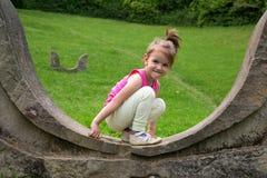 蹲下在斯通沃尔和看照相机的可爱的微笑的小女孩在公园 免版税库存图片