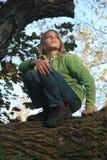 蹲下在树枝的男孩 免版税库存照片