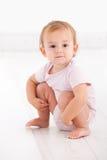 蹲下在楼层上的逗人喜爱的女婴 库存图片