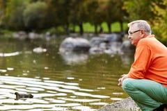 蹲下在池塘附近的成熟人 库存图片