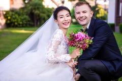 蹲下在草坪的愉快的婚礼夫妇画象  免版税图库摄影