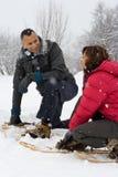 蹲下在雪佩带的雪靴的夫妇 库存照片