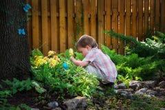 蹲下在寻找的小男孩复活节彩蛋下 免版税库存图片
