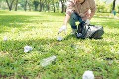 蹲下浪费和接它在容器袋子的年轻人 免版税库存照片