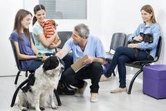 蹲下由宠物和所有者的男性护士在等候室 免版税库存照片