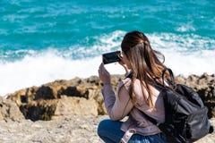 蹲下的妇女为与智能手机的岸照相 免版税图库摄影