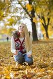 蹲下的少妇,当查寻在公园在秋天期间时 免版税库存图片