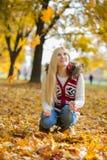 蹲下的少妇,当查寻在公园在秋天期间时 库存图片