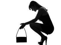 蹲下的绝望剪影时髦的thinkig妇女 免版税库存照片