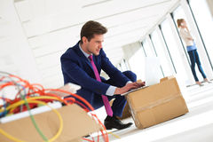 蹲下年轻的商人,当使用在纸板箱的膝上型计算机在新的办公室时 免版税图库摄影
