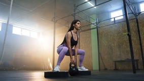 蹲与kettlebells的确信的体育妇女在手上在crossfit健身房 股票录像