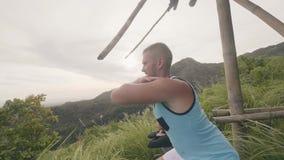 蹲健身的夫妇,当在绿色高地背景时的室外训练 体育男人和妇女训练蹲坐 影视素材