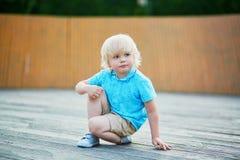 蹲在他的在操场的腰臀部分的小男孩 免版税库存照片