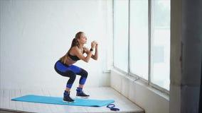蹲坐 做蹲坐的可爱的少妇在健身演播室 在健身房的场面 股票视频