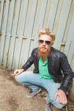 年轻蹲的有胡子的人 库存照片
