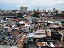 蹲着的人棚子和议院在贫民窟市区 图库摄影