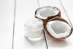 身体关心的椰子油在白色书桌嘲笑的化妆概念 免版税图库摄影
