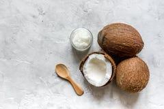 身体关心的椰子油在石书桌上的化妆概念 免版税库存照片