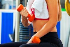身体局部体育女孩在健身房的推力哑铃 二头肌前景 免版税库存照片