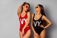 身体泳装和太阳镜的两个年轻性感的女孩在演播室 库存图片