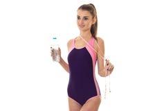 身体泳装的年轻性感的亭亭玉立的深色的夫人有措施磁带和瓶的在她被隔绝的手微笑的水  免版税图库摄影