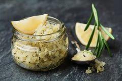 身体洗刷海盐用柠檬、迷迭香和橄榄油在玻璃瓶子在石桌上 免版税图库摄影