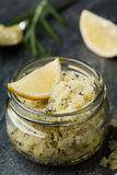 身体洗刷海盐用柠檬、迷迭香和橄榄油在玻璃瓶子在石桌上 免版税库存图片