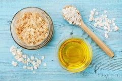 身体洗刷燕麦粥、糖、蜂蜜和油在玻璃瓶子在蓝色土气桌上,自创化妆用品剥皮的和温泉 免版税库存图片