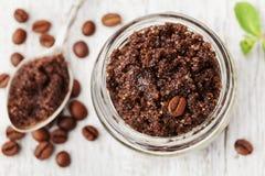身体洗刷碾碎的咖啡、糖和椰子油在玻璃瓶子在白色土气桌上,自创化妆用品剥皮的和温泉 库存图片