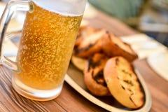 满身是汗的杯子冰镇啤酒在一个热的夏日,与泡影visibl 库存照片
