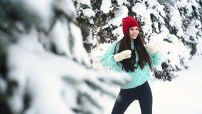 身着暖蓝色针织毛衣和红帽的漂亮年轻女人,在一个背景下玩得开心,跳舞 影视素材