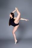 黑紧身衣裤的年轻女性柔术表演者在黑暗的背景 库存图片