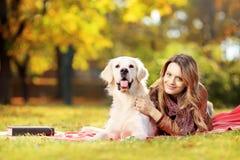 躺下与她的狗的美丽的女性在公园 免版税图库摄影