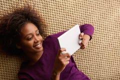 躺下与数字式片剂的微笑的妇女 免版税库存照片