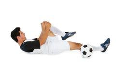 躺下和呼喊在痛苦中的足球运动员 免版税库存图片