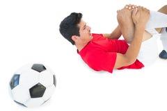 躺下和呼喊在痛苦中的足球运动员 免版税图库摄影