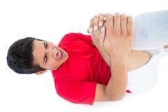 躺下和呼喊在痛苦中的足球运动员 免版税库存照片