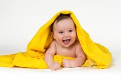 躺下和微笑在一块黄色毛巾的新出生的婴孩 库存图片