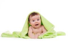 躺下和微笑在一块绿色毛巾的新出生的婴孩 免版税库存图片