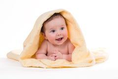躺下和微笑在一块黄色毛巾的新出生的婴孩 免版税库存图片
