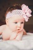 躺下在一张白色床上的逗人喜爱的女婴画象  大开放眼睛 在诞生之后的健康小孩 库存图片