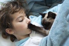 躺下在与她的猫的床上的小女孩 库存图片