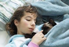 躺下在与她的猫的床上的小女孩 库存照片