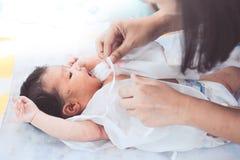 躺下在她的床上的逗人喜爱的亚裔新出生的女婴 图库摄影