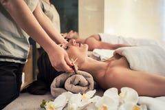 躺下在按摩床上的轻松的妇女在面部治疗期间 免版税图库摄影