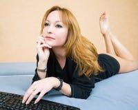 躺下在沙发的金发碧眼的女人 图库摄影