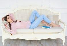 躺下在沙发的轻松的少妇 免版税库存照片