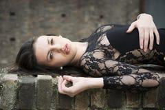 躺下在砖墙上的俏丽的深色的少妇 库存照片